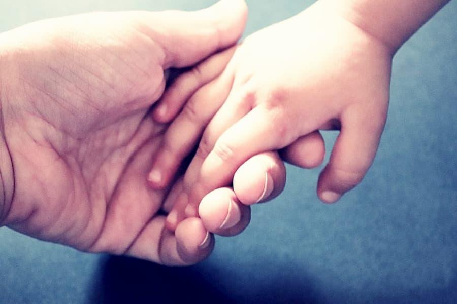 Le parent tient la main de l'enfant