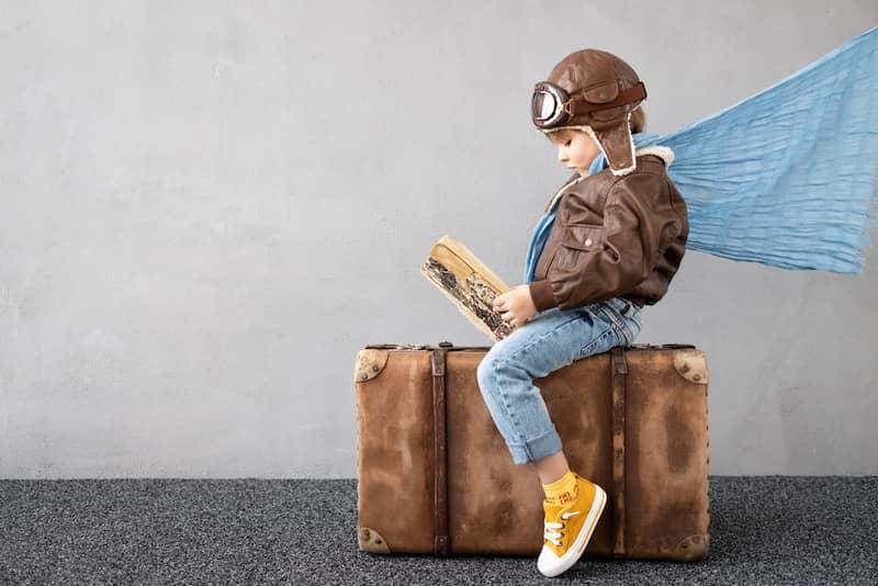 Enfant lit un livre et voyage