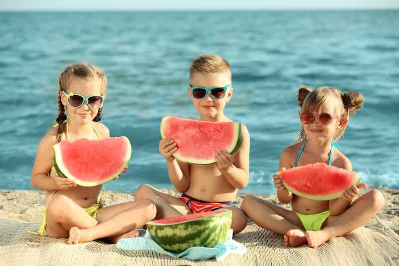 Enfants mangent de la pastèque à la plage
